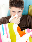 Diseased young man with tissues lying on the sofa — Stock Photo