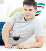 Handsome young man with wineglass lying on the floor — Stock Photo