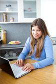 Bright caucasian woman using her laptop in the kitchen — Stok fotoğraf