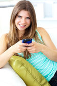 Smiling young woman texting sitting on the sofa — Stock Photo