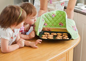 Smiling woman baking with her daughters — Stock Photo