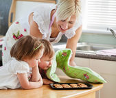 Smiling woman baking cookies with her daughters — Stock Photo