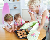 Pretty woman baking cookies with her daughter — Stock Photo