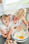 Cute woman baking cookies with her daughter — Stock Photo