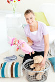 Cheerful caucasian woman putting toys into a basket — Stock Photo
