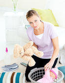 Depressed young mother putting toy into a basket — Stock Photo