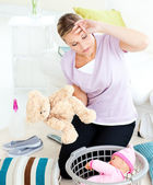 Exhausted young woman putting toys into a basket — Stock Photo