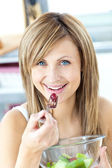 Jolly woman eating a fruit salad smiling at the camera — Stock Photo