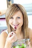 Jolly woman eating a fruit salad smiling at the camera — Stock Photo