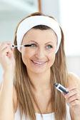 Glowing young woman using mascara — Stock Photo