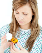Concentrated female patient looking at her pills — Stock Photo