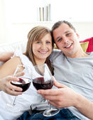 Loving young couple drinking wine sitting on a sofa — Stock Photo