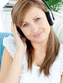 Portrait of a delighted woman listen to music with headphones — Stock Photo