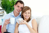 Attentive young couple drinking coffe sitting on a sofa — Stock Photo