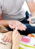 Close-up of young man giving pills to his morbid girlfriend — Stock Photo