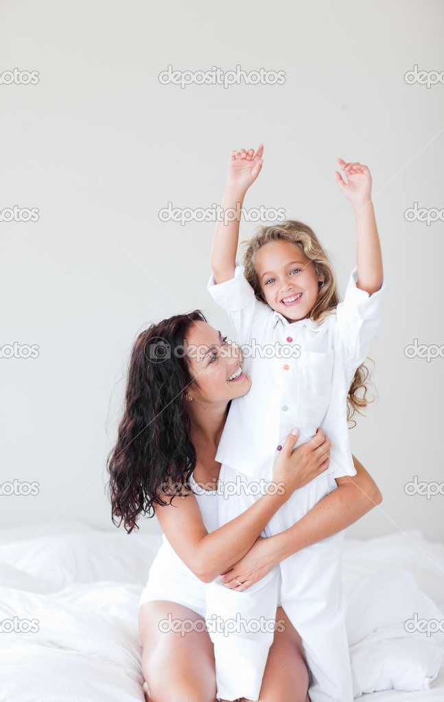 Happy young family having fun together on the bed — Stock Photo #10820724