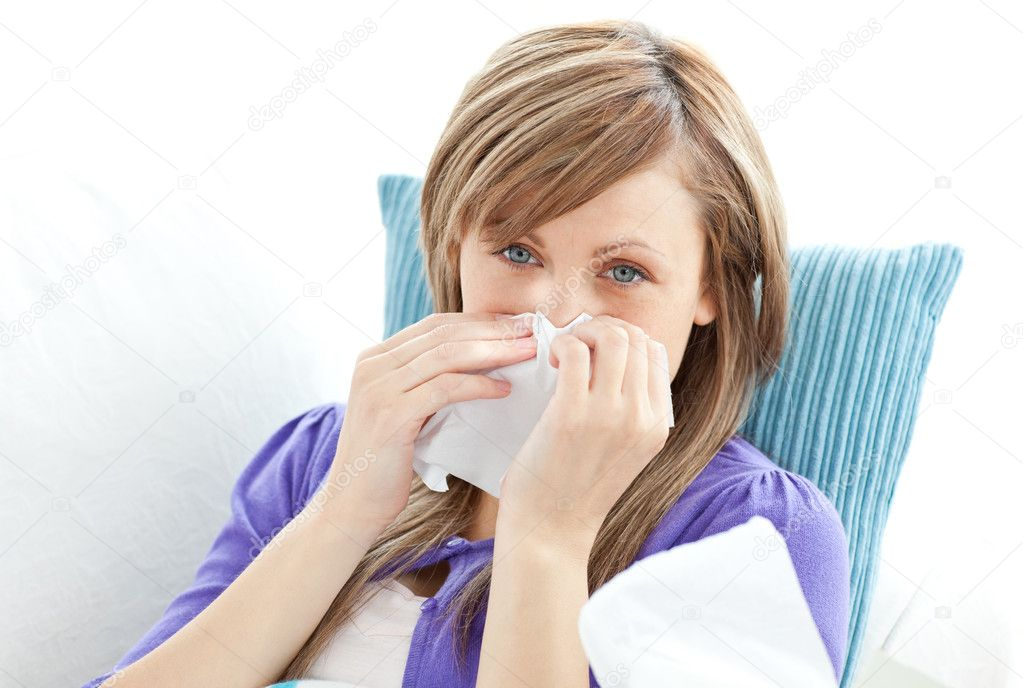 Portrait of a sick pretty woman blowing lying on a sofa against white background — Stock Photo #10824620