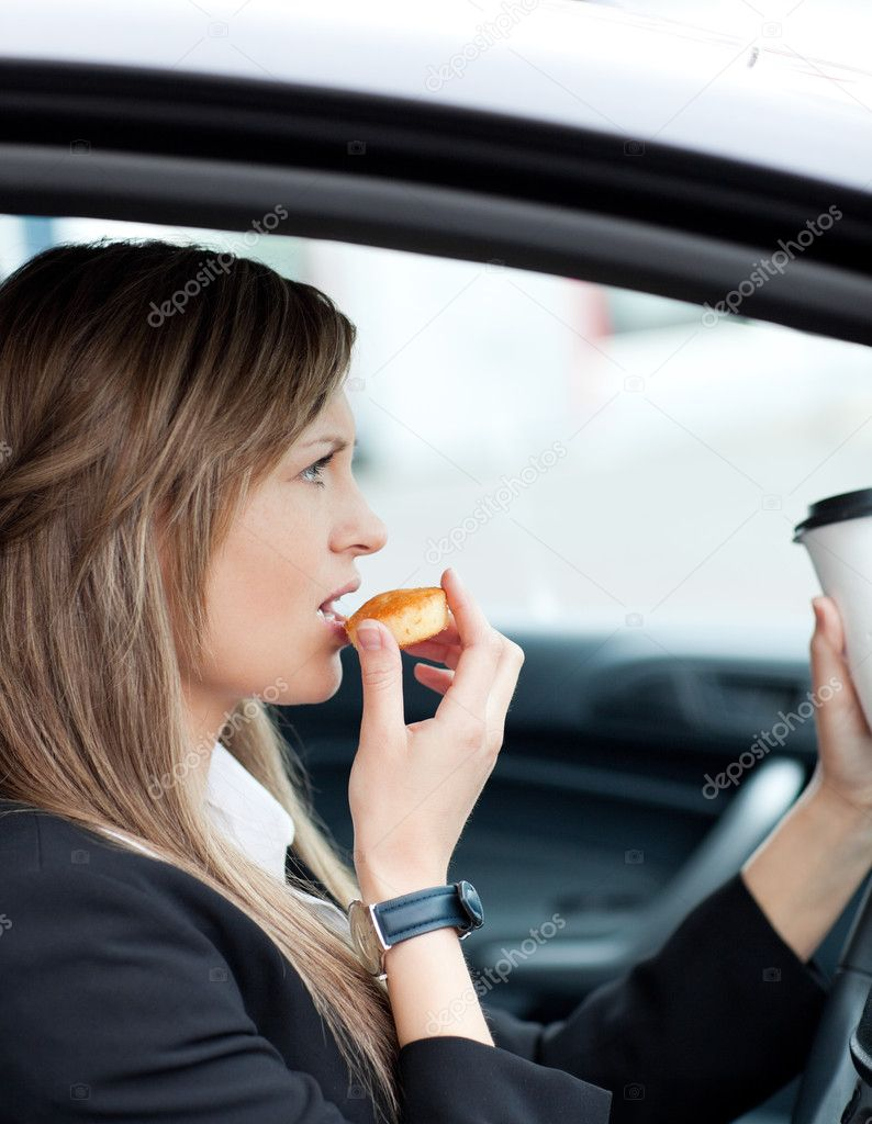 Attractive businesswoman eating and holding a drinking cup while driving to work  Stock Photo #10824920