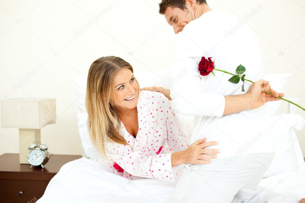 Attentive man giving a rose to his wife in the bedroom  Stock Photo #10825736