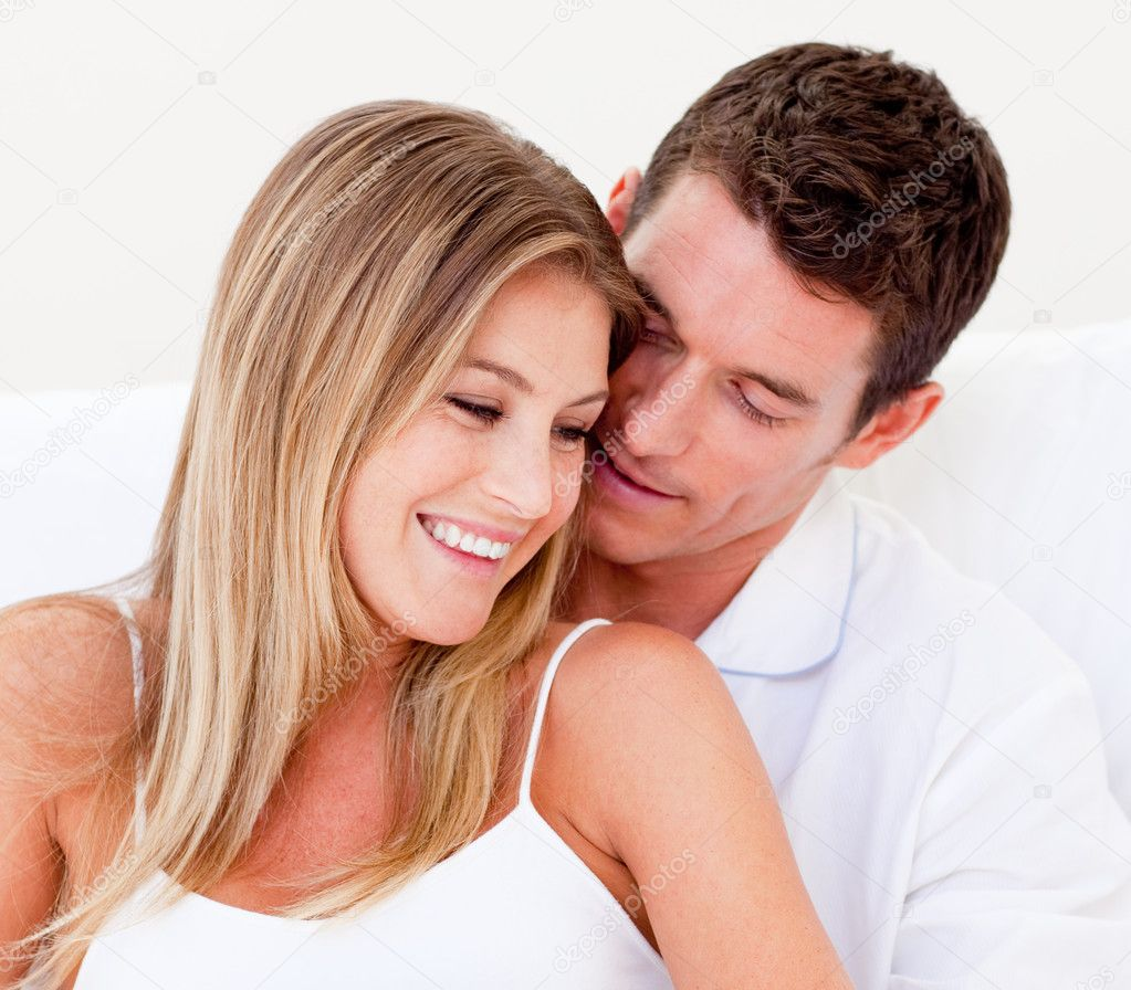 Portrait of an affectionate couple sitting on bed  at home  Stock Photo #10825755