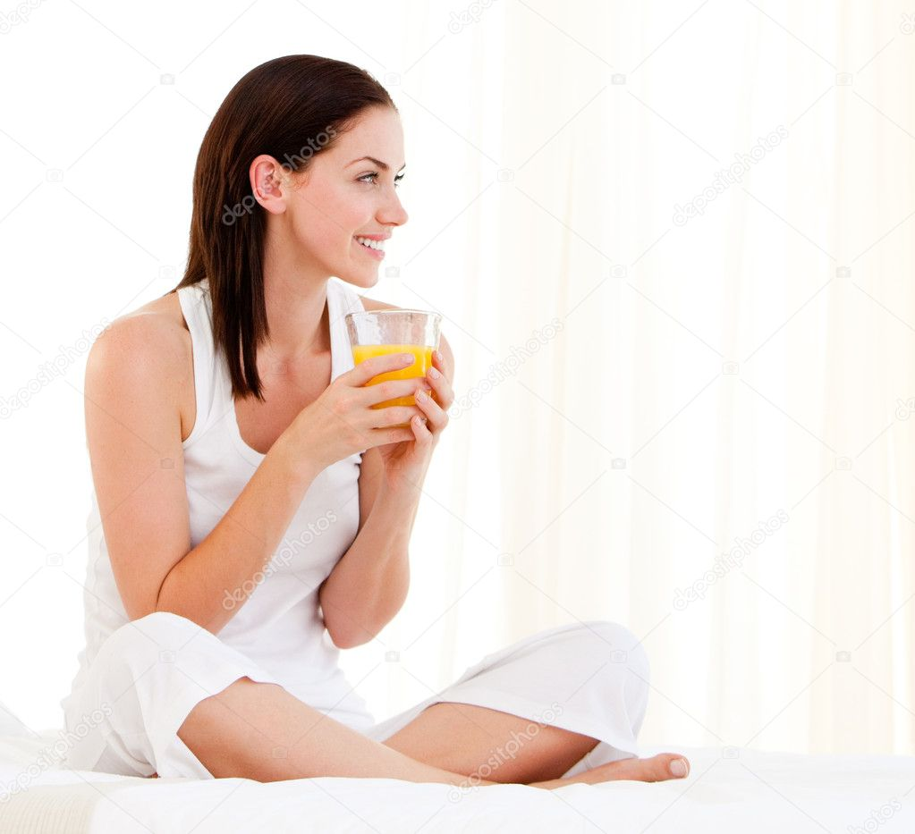 Cheerful woman drinking an orange juice sitting on her bed at home — Stock Photo #10825964