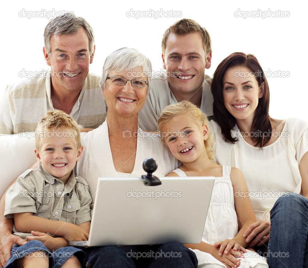 Happy family sitting on sofa using a laptop at home — Stock Photo #10826119