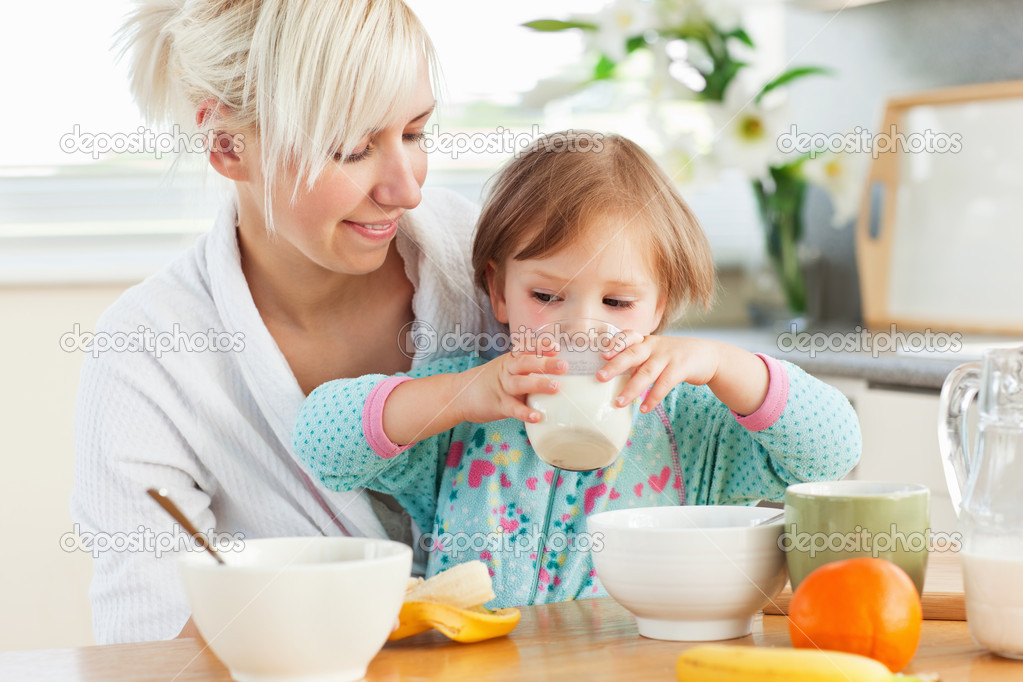 Radiant woman having breakfast with her daughter in kitchen — Stock Photo #10829494