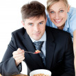 Enamored couple of businesspeople smiling at camera eating cerea — Stock Photo #10830049