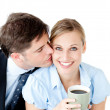 Attentive businessman kissing his girlfriend at her cheek — Stock Photo
