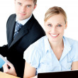 Beautiful couple of businesspeople smiling at camera using lapto - Stock Photo