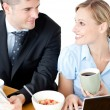 Affectionate young couple having breakfast using their laptop — Stock Photo