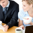Happy couple of businesspeople having breakfast reading the news — Stock Photo