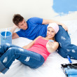 Attentive couple relaxing after paiting a room — Stock Photo