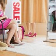 Female friends trying clothes in a changing room — Stock Photo