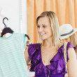 Caucasian blond woman looking at a shirt in a clothes store — Stock Photo #10830133