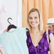 Happy blond woman looking at a shirt in a clothes store — Stock Photo #10830136