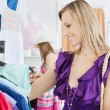 Elegant young woman choosing clothes with her friend — Stock Photo #10830139