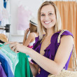 Joyful young woman choosing clothes with her friend — Stockfoto