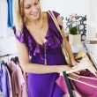 Young caucasian woman choosing a dress — Stock Photo