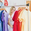 Merry blond woman choosing colorful clothes — Stock Photo #10830174
