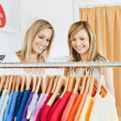 joyful female friends choosing colorful shirts — Stock Photo