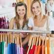 Bright female friends doing shopping smiling at the camera — Stock Photo