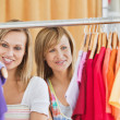 Beautiful female friends doing shopping choosing shirts — Stock Photo
