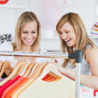 Pretty female friends doing shopping choosing shirts — Foto Stock