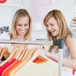 Pretty female friends doing shopping choosing shirts — Stock Photo