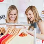 Pretty female friends doing shopping choosing shirts — Stock Photo
