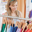 Captivating young woman choosing a colorful shirt — Stock Photo