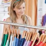 Captivating young woman choosing a colorful shirt — Stock Photo