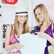 Delighted friends looking at a shirt in a clothes store — Stock Photo #10830250