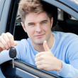 Stock Photo: Positive young mholding key sitting in car